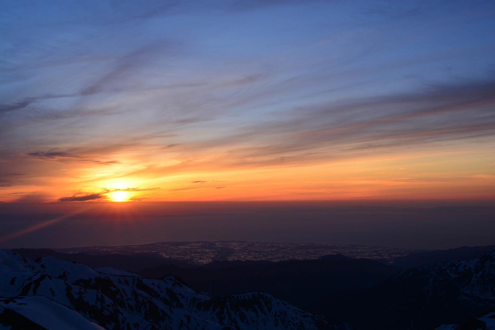 「残雪の山から見る日本海に沈む夕日」の写真