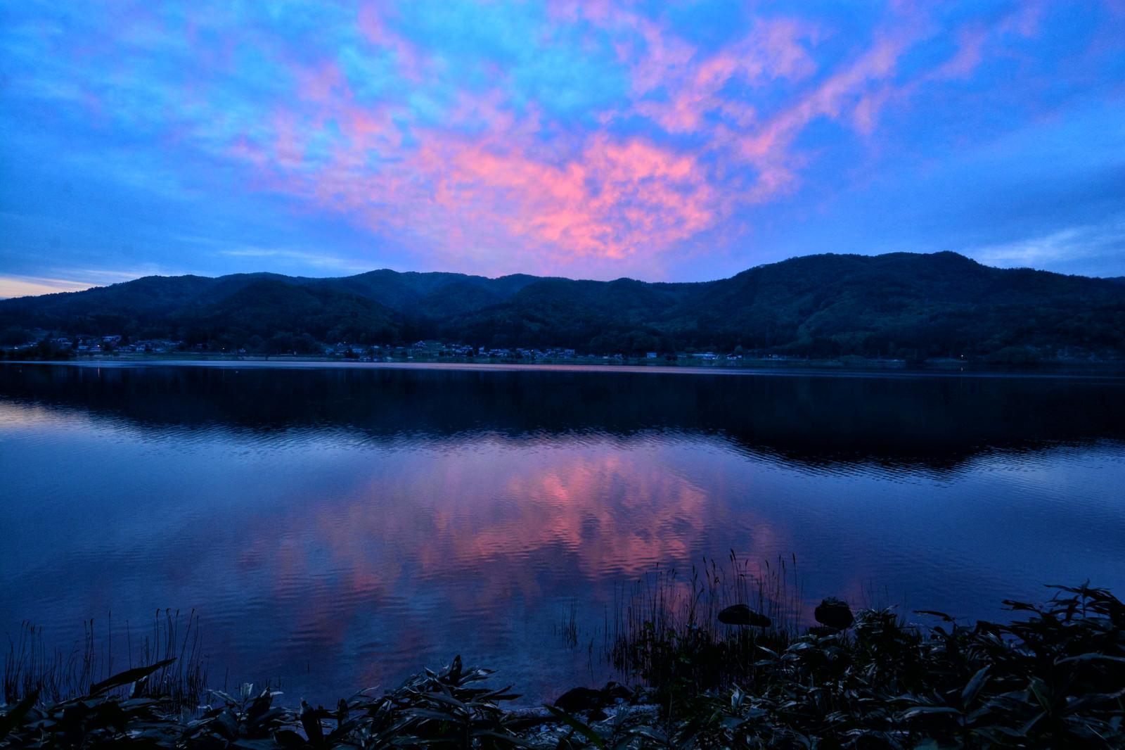 「湖面に映るリフレクションした夕焼けの空」の写真