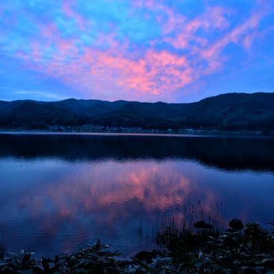 湖面に映るリフレクションした夕焼けの空の写真