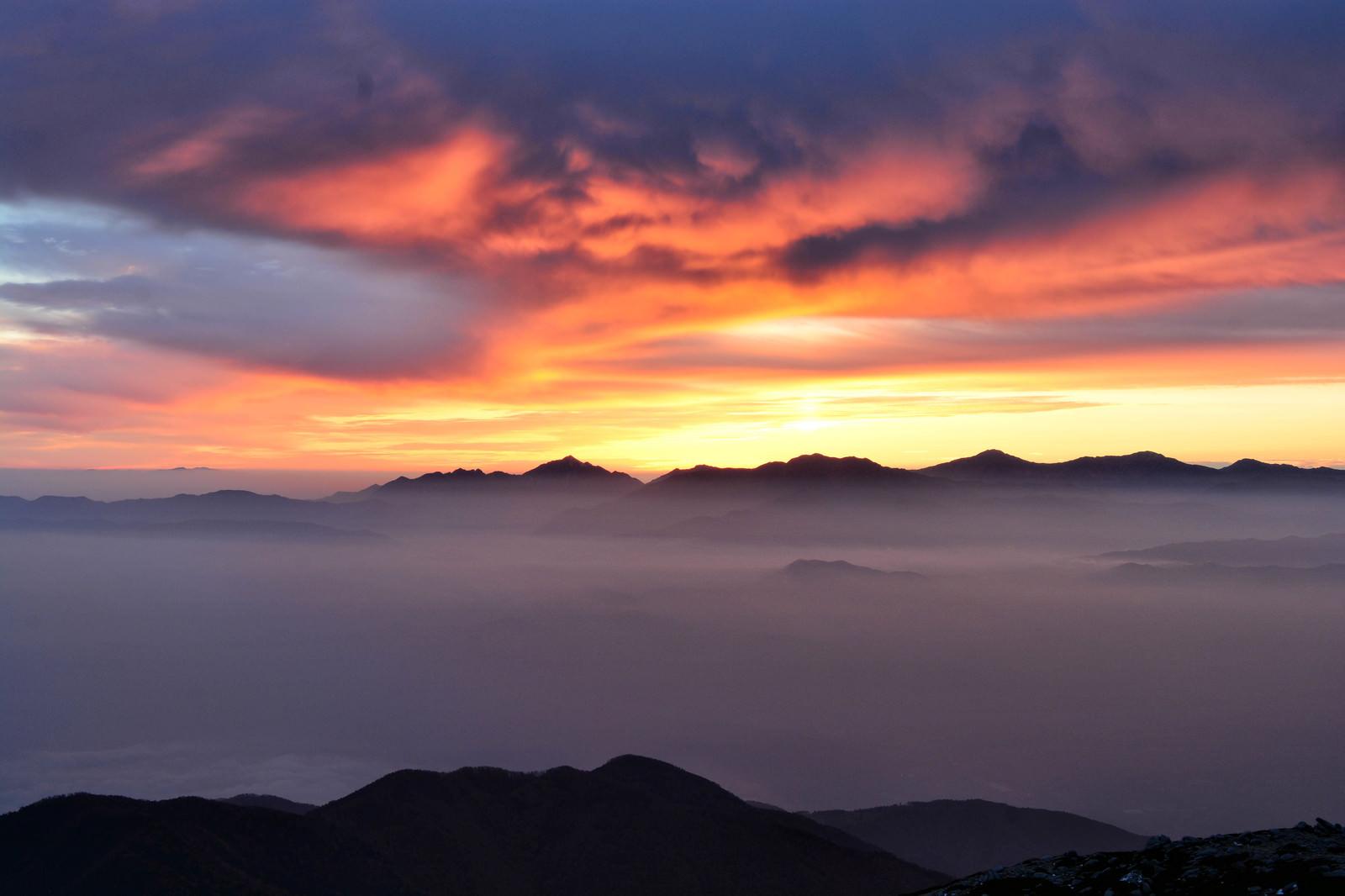 「夕焼けに染まる南アルプスのシルエットと雲海の様子」の写真