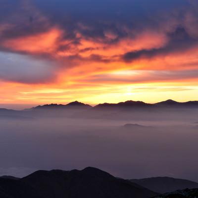 夕焼けに染まる南アルプスのシルエットと雲海の様子の写真