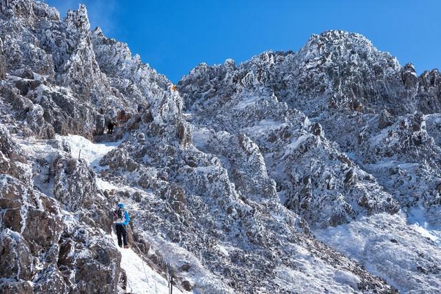 岩と氷の山に挑戦する登山者の写真