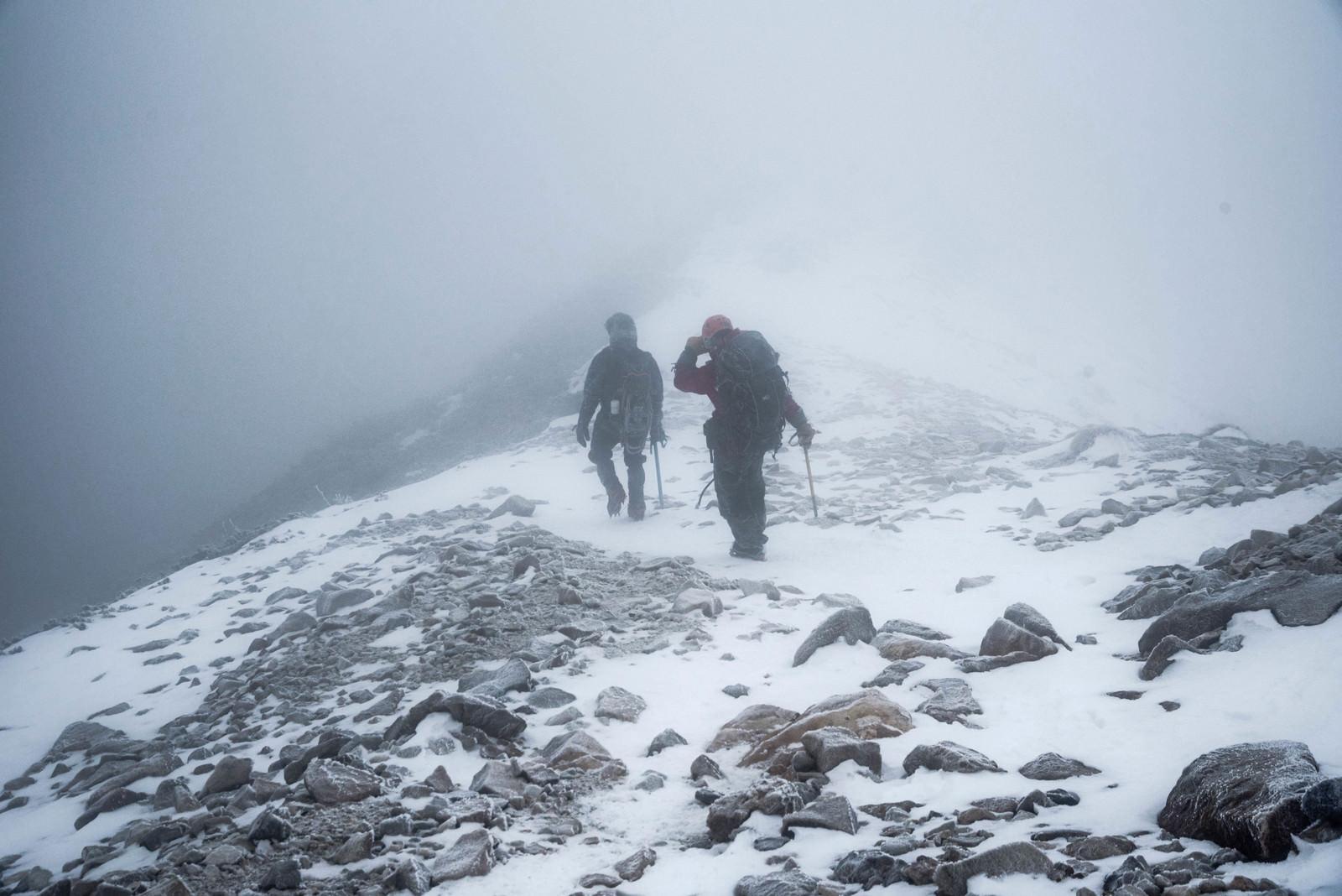 「ホワイトアウト発生時に下山する登山者」の写真