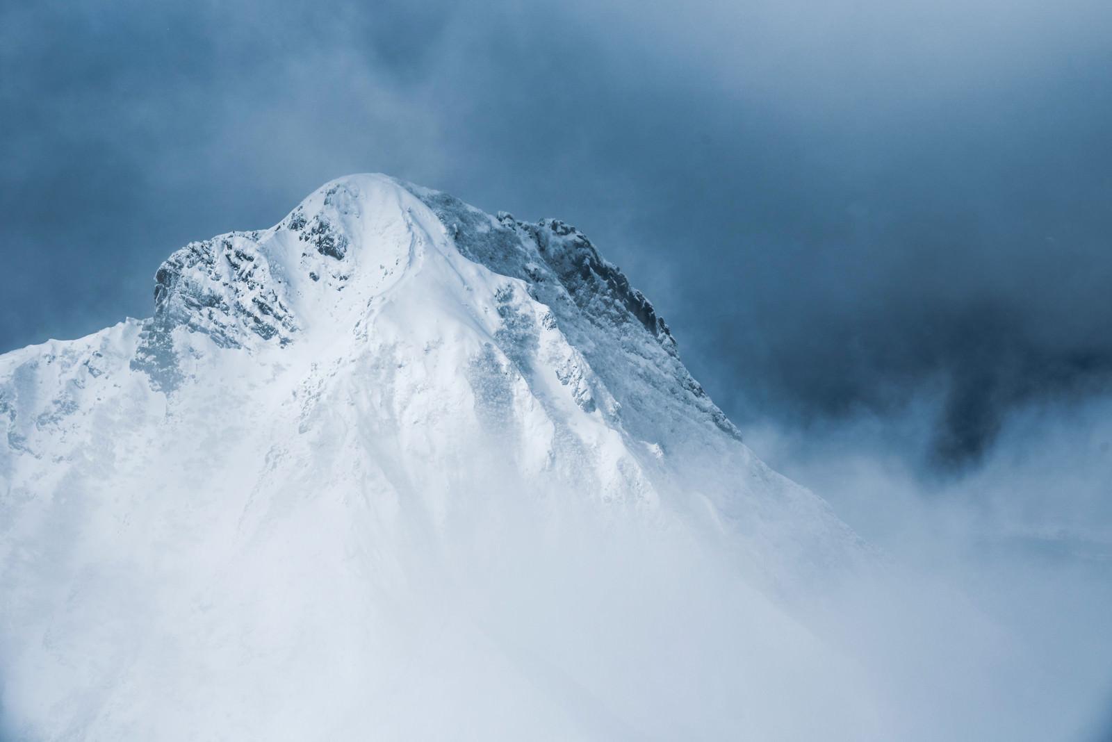 「灰色の雲の切れ間から姿を出した阿弥陀岳(八ヶ岳南部)」の写真