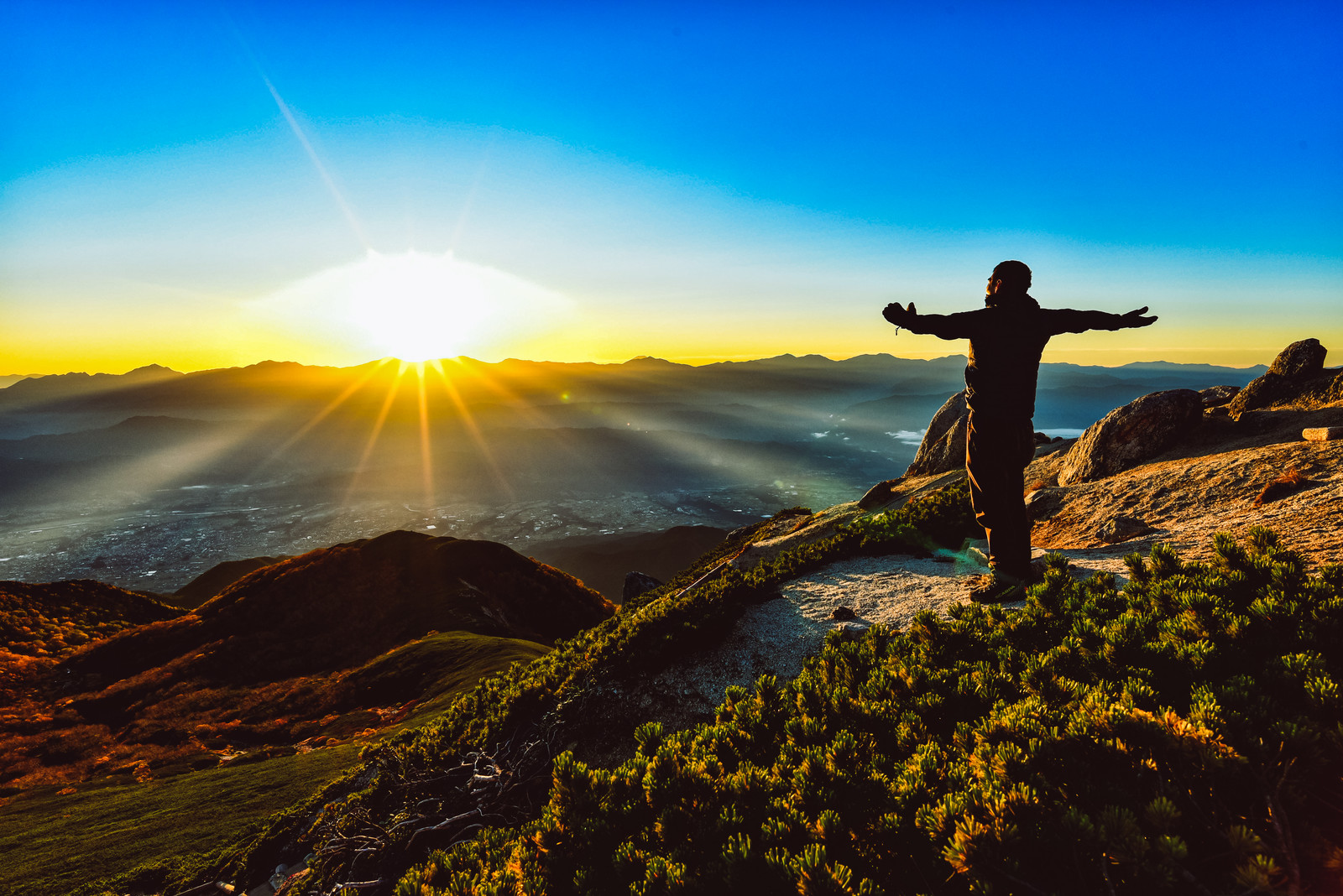 「朝日を全身に浴びる登山者」の写真