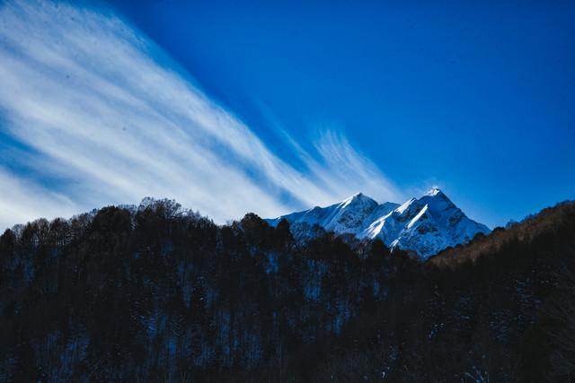 冬山から続く巻雲の写真
