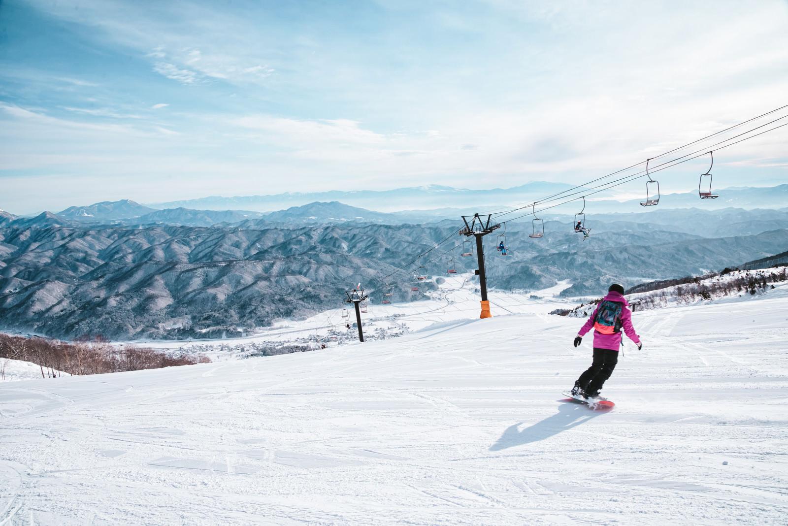 「ゲレンデを滑るスノーボーダーとリフト」の写真