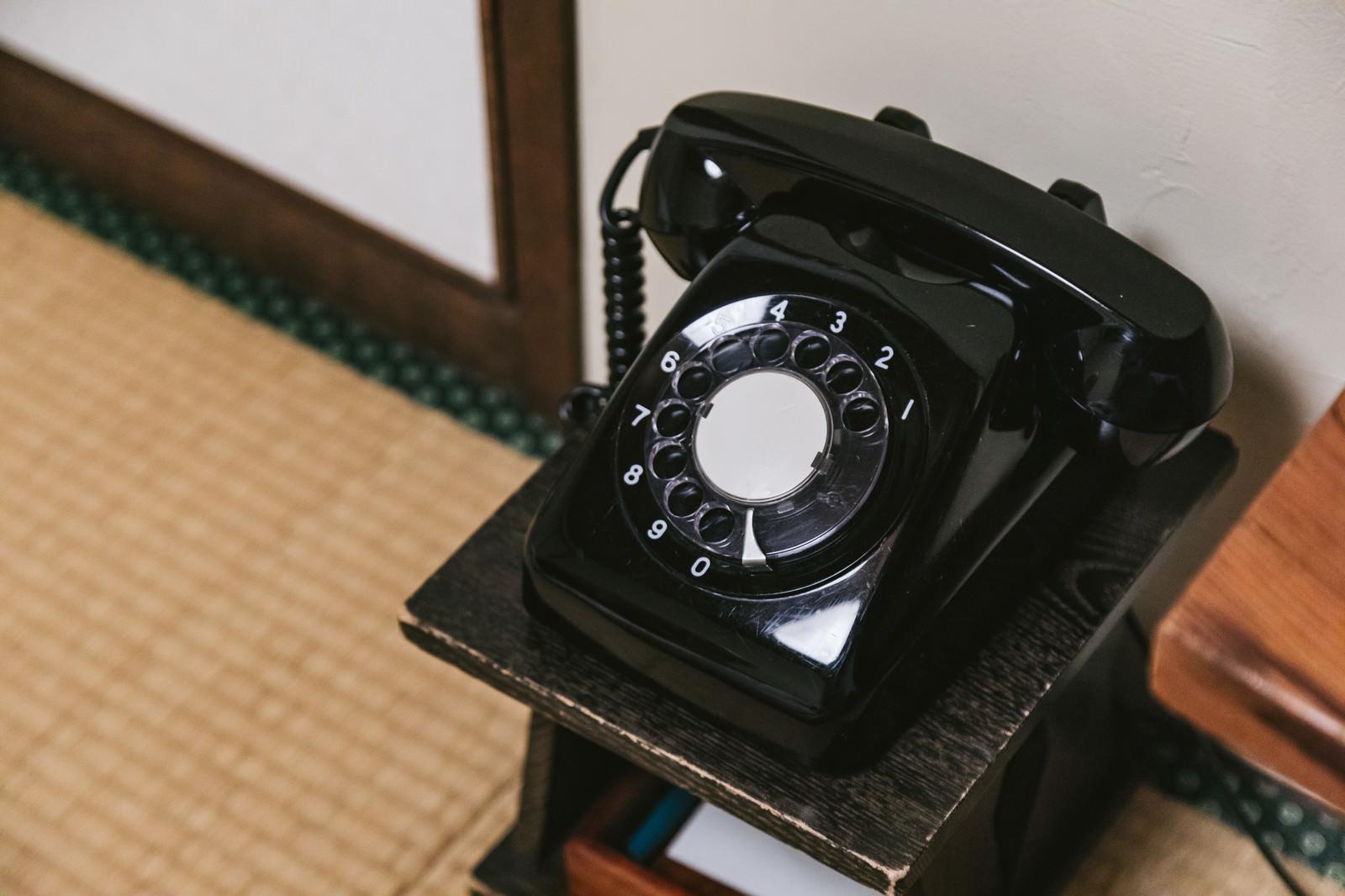 「和室の片隅に置かれた黒電話」の写真