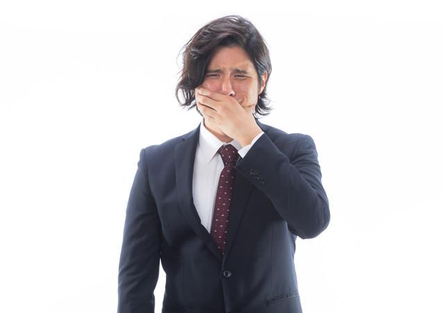口を抑えて苦しむ男性会社員の写真