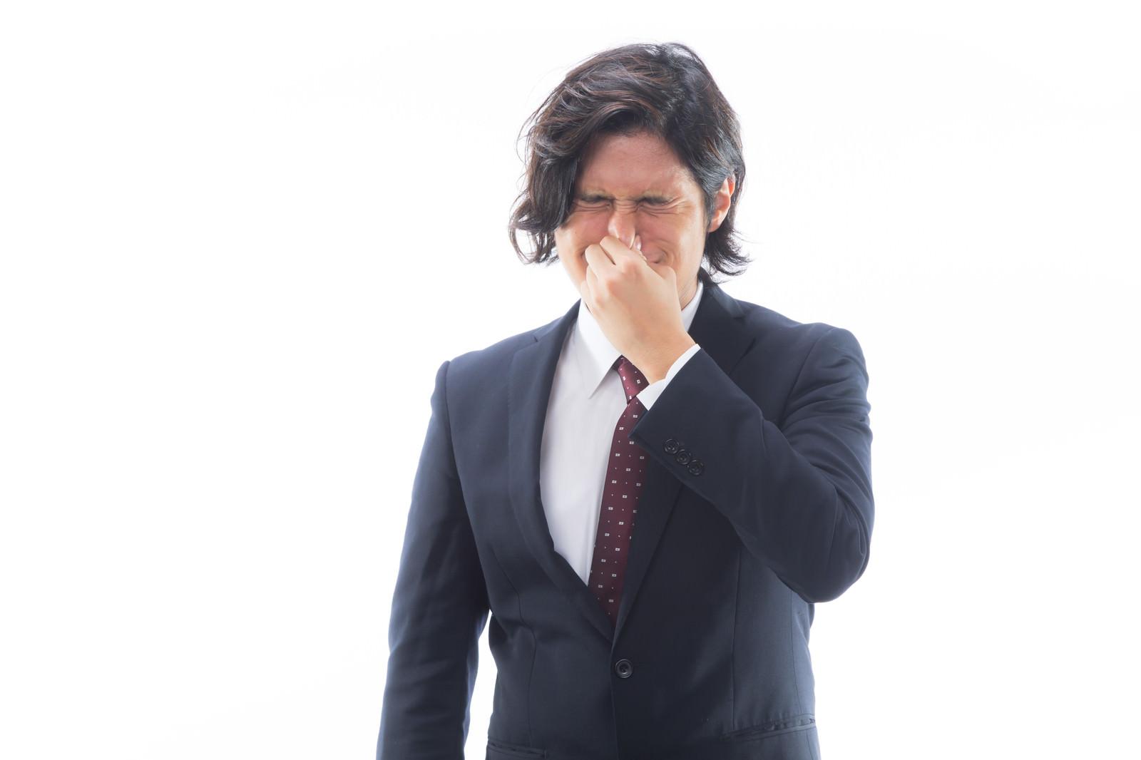 「目がしみるほどの強烈なにおいを嗅ぐ男性会社員」の写真[モデル:竹田匡宏]