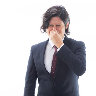 目がしみるほどの強烈なにおいを嗅ぐ男性会社員の写真
