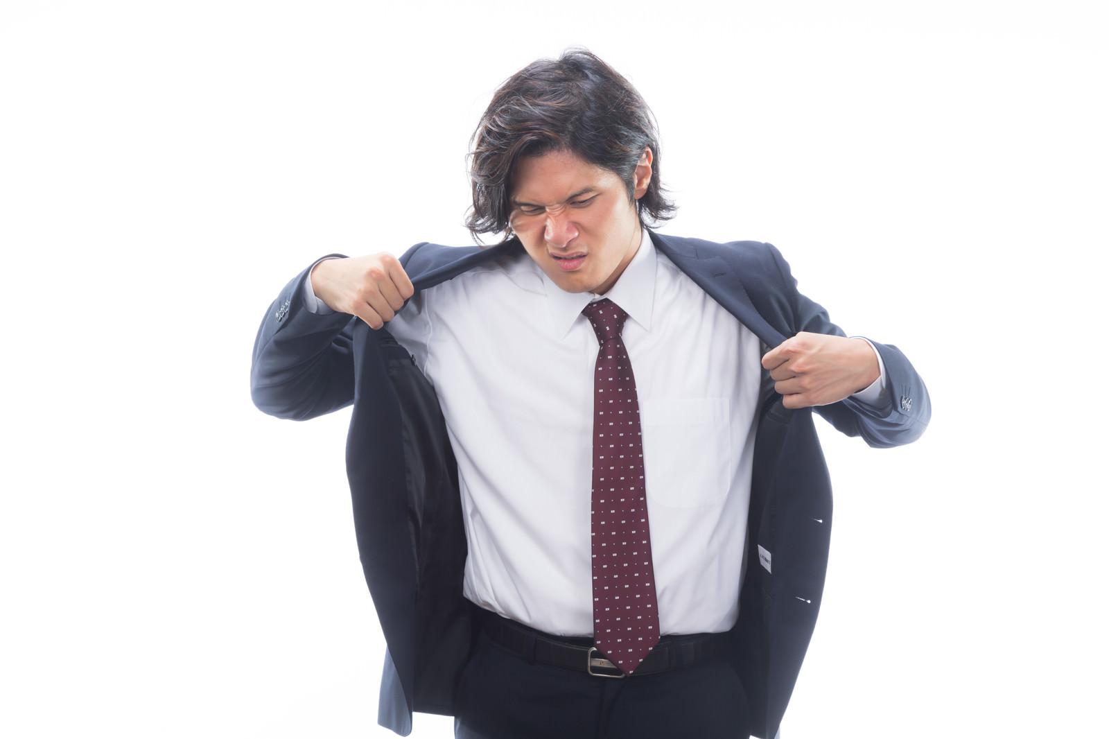 「汗をかいて上着を脱ぐサラリーマン」の写真[モデル:竹田匡宏]