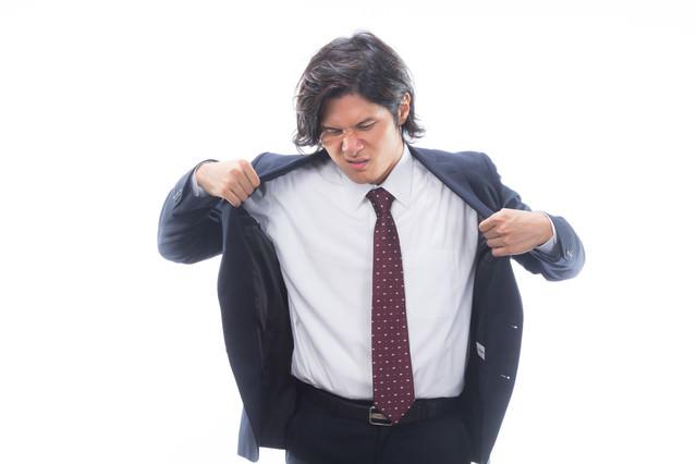 汗をかいて上着を脱ぐサラリーマンの写真