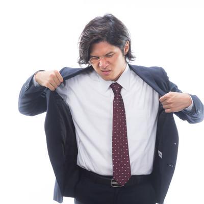 「汗をかいて上着を脱ぐサラリーマン」の写真素材