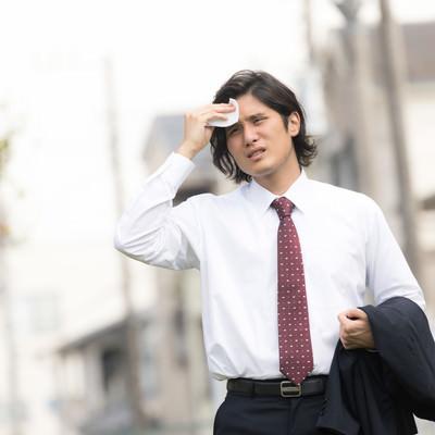 額の汗を拭う飛び込み営業マンの写真