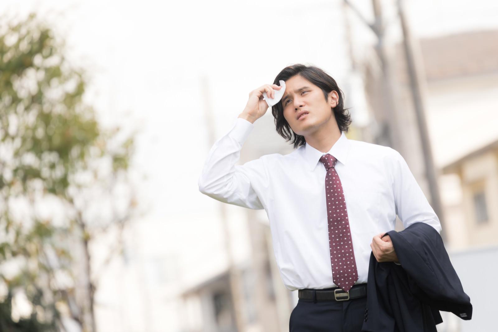 「暑くて上着を脱ぐサラリーマン(営業中の外回り)」の写真[モデル:竹田匡宏]