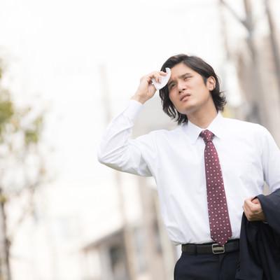 暑くて上着を脱ぐサラリーマン(営業中の外回り)の写真