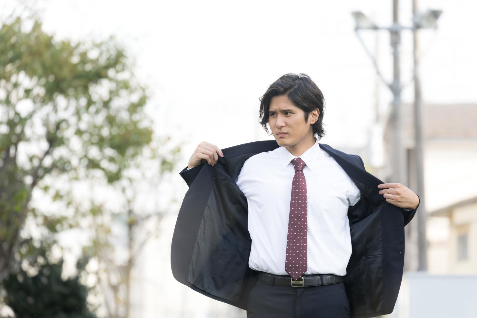 「脇汗を気にして上着を脱ぐ外出中のサラリーマン」の写真[モデル:竹田匡宏]