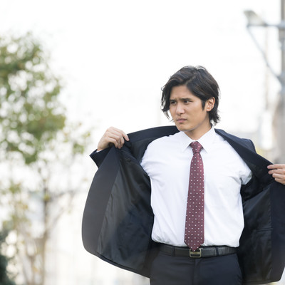 「脇汗を気にして上着を脱ぐ外出中のサラリーマン」の写真素材