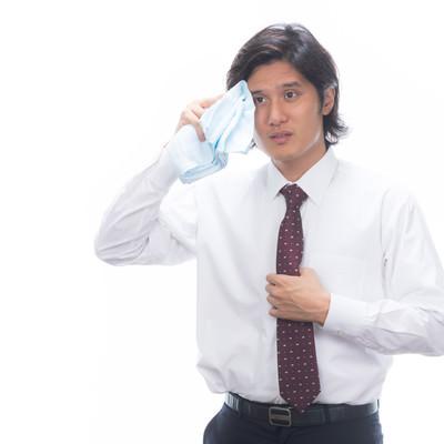 暑さに息切れしている汗かきの男性の写真