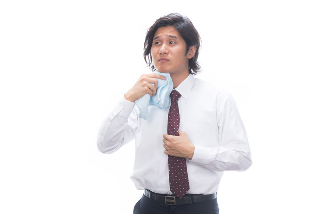 タオルで汗を拭くサラリーマンの写真