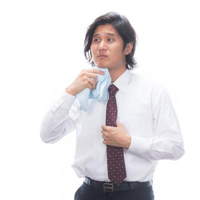「タオルで汗を拭くサラリーマン」の写真素材