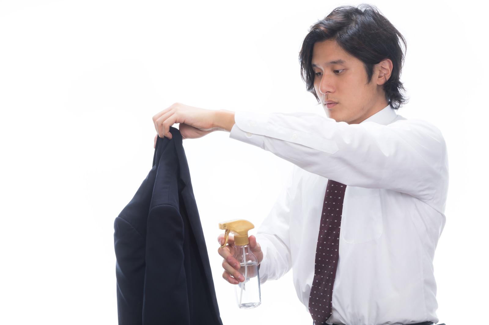 「上着に消臭スプレーをかける会社員」の写真[モデル:竹田匡宏]