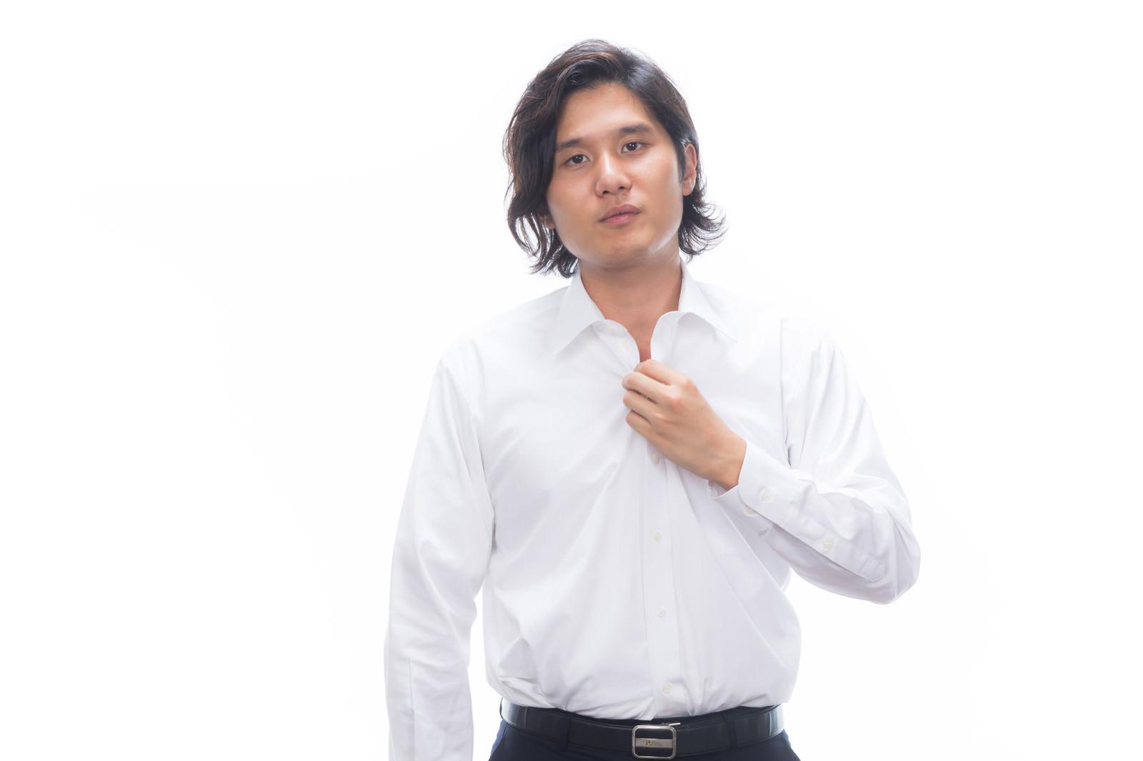 「ワイシャツのボタンを外す男性」の写真[モデル:竹田匡宏]