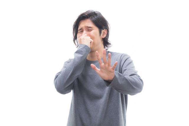 耐え難い悪臭で顔を背ける男性の写真