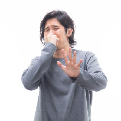 「耐え難い悪臭で顔を背ける男性」の写真素材