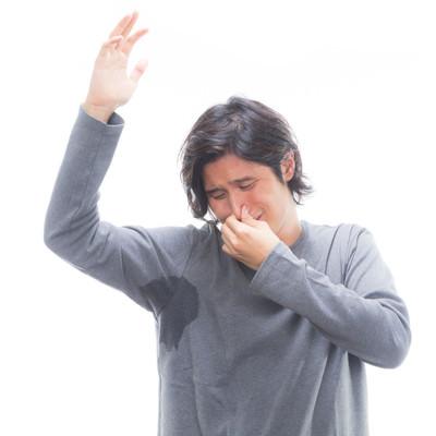 自分のワキの臭いに思わず鼻をつまむ男性の写真
