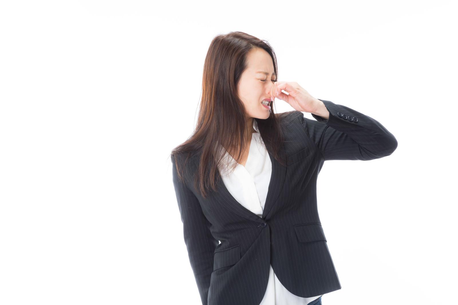 「顔を背けて鼻をつまむ女性」の写真[モデル:土本寛子]