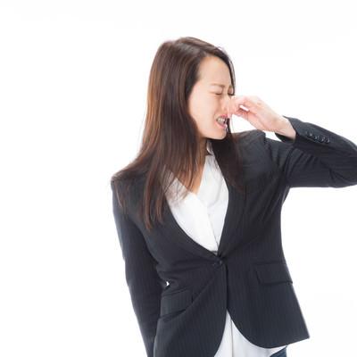 「顔を背けて鼻をつまむ女性」の写真素材