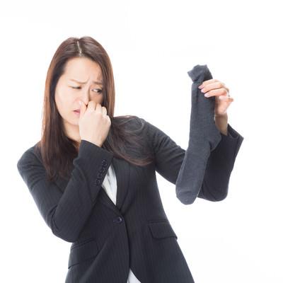「靴下から発する悪臭で鼻をつまむオフィスレディ」の写真素材
