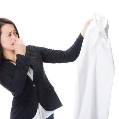 「悪臭がする男性のワイシャツを片手に露骨に嫌がる女性社員」の写真素材