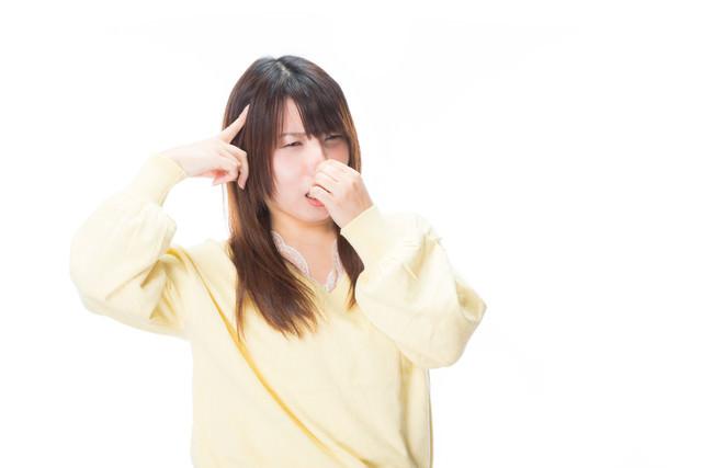 悪臭で頭痛がひどい女性の写真