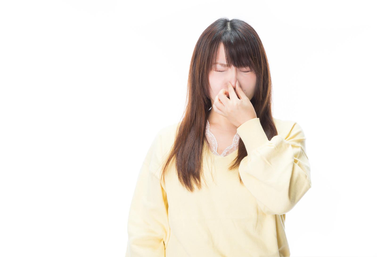「衝撃的なにおいに思わず目を閉じる女性」の写真[モデル:Lala]