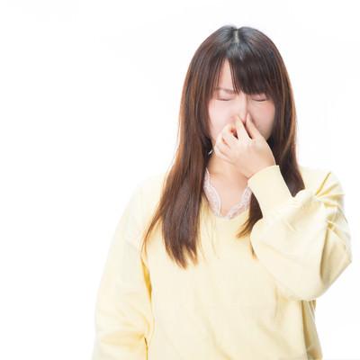「衝撃的なにおいに思わず目を閉じる女性」の写真素材