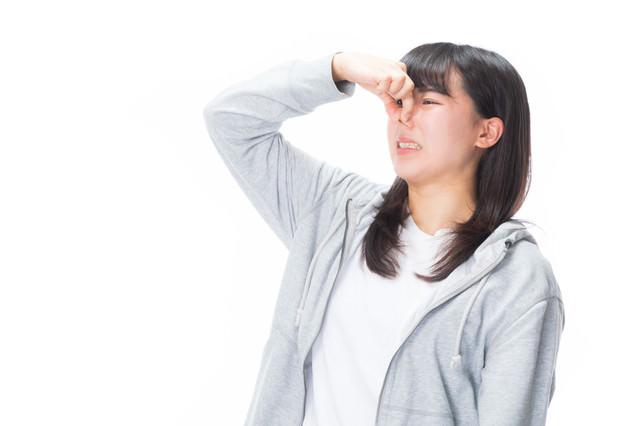顔を歪めて臭さをアピールする女性の写真