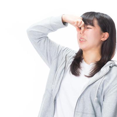 「顔を歪めて臭さをアピールする女性」の写真素材