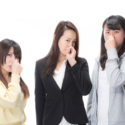 「露骨に鼻をつまむ女性スタッフ」の写真素材