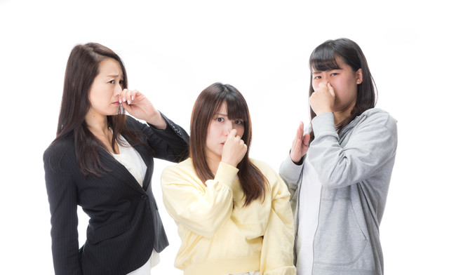 くさくて鼻をつまむ女性たちの写真