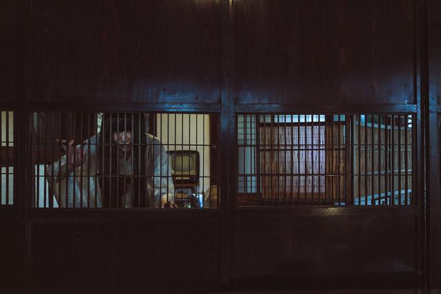 古民家の格子戸越しに覗き見る女性の姿の写真