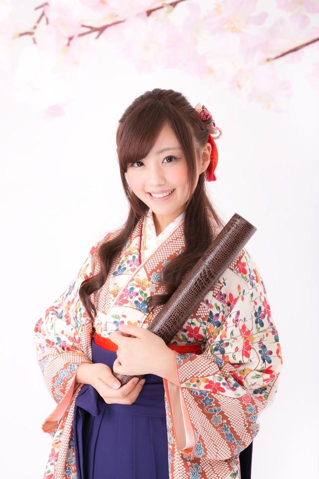 卒業証書を持った袴姿の女性の写真