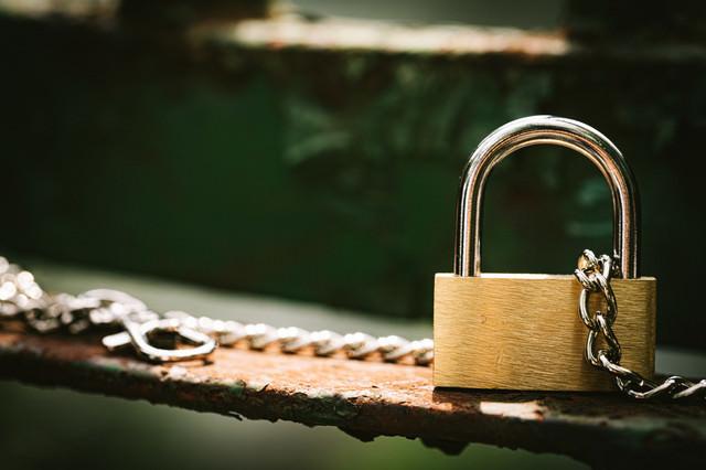 鎖に繋がれる南京錠の写真