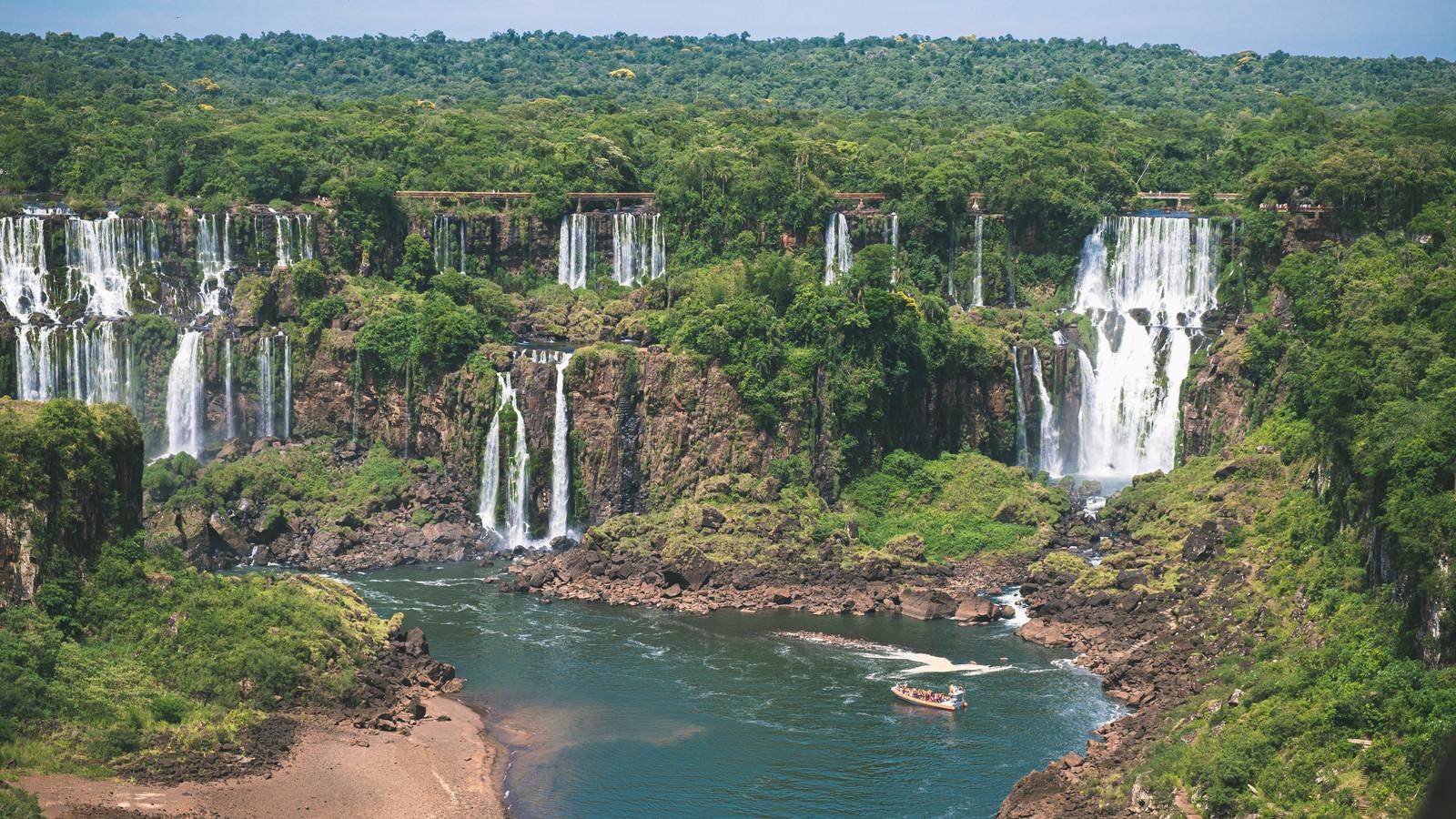 「ジャングルに覆われたイグアス川と観光ボート(南米大陸)」の写真