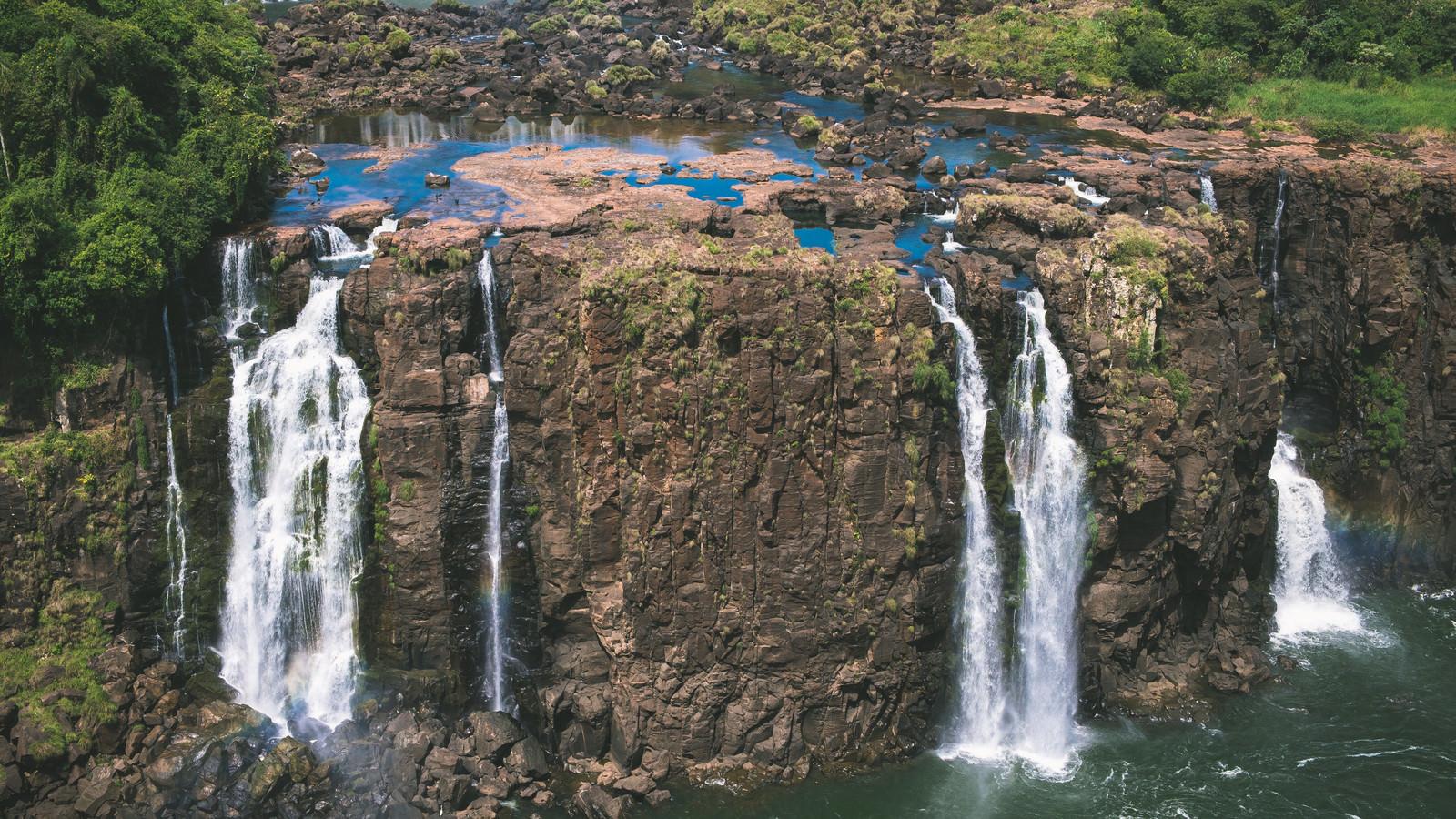 「切り立った岩壁と所々に虹(イグアスの滝)」の写真