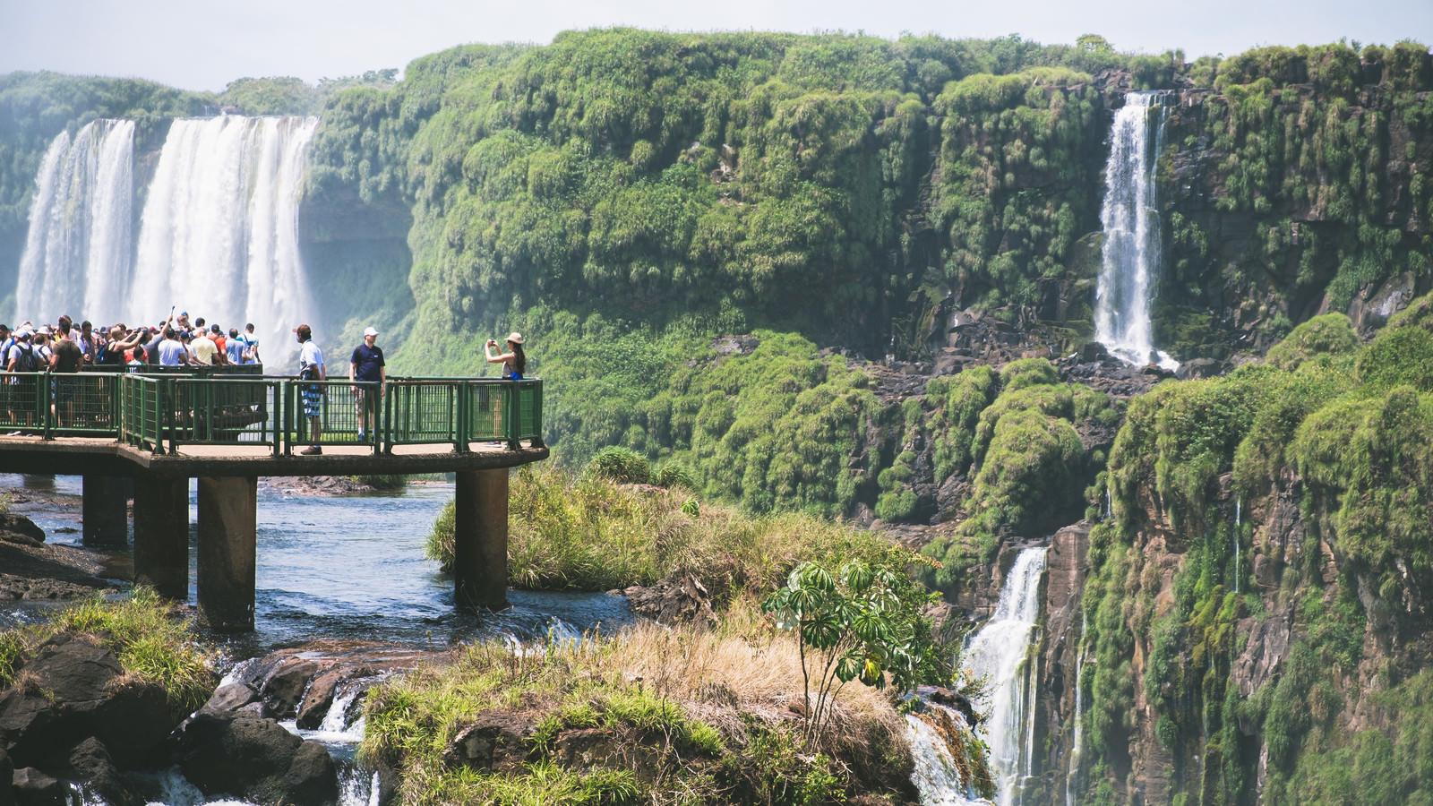 「絶景間近で撮影する観光客とイグアスの滝(南米大陸)」の写真
