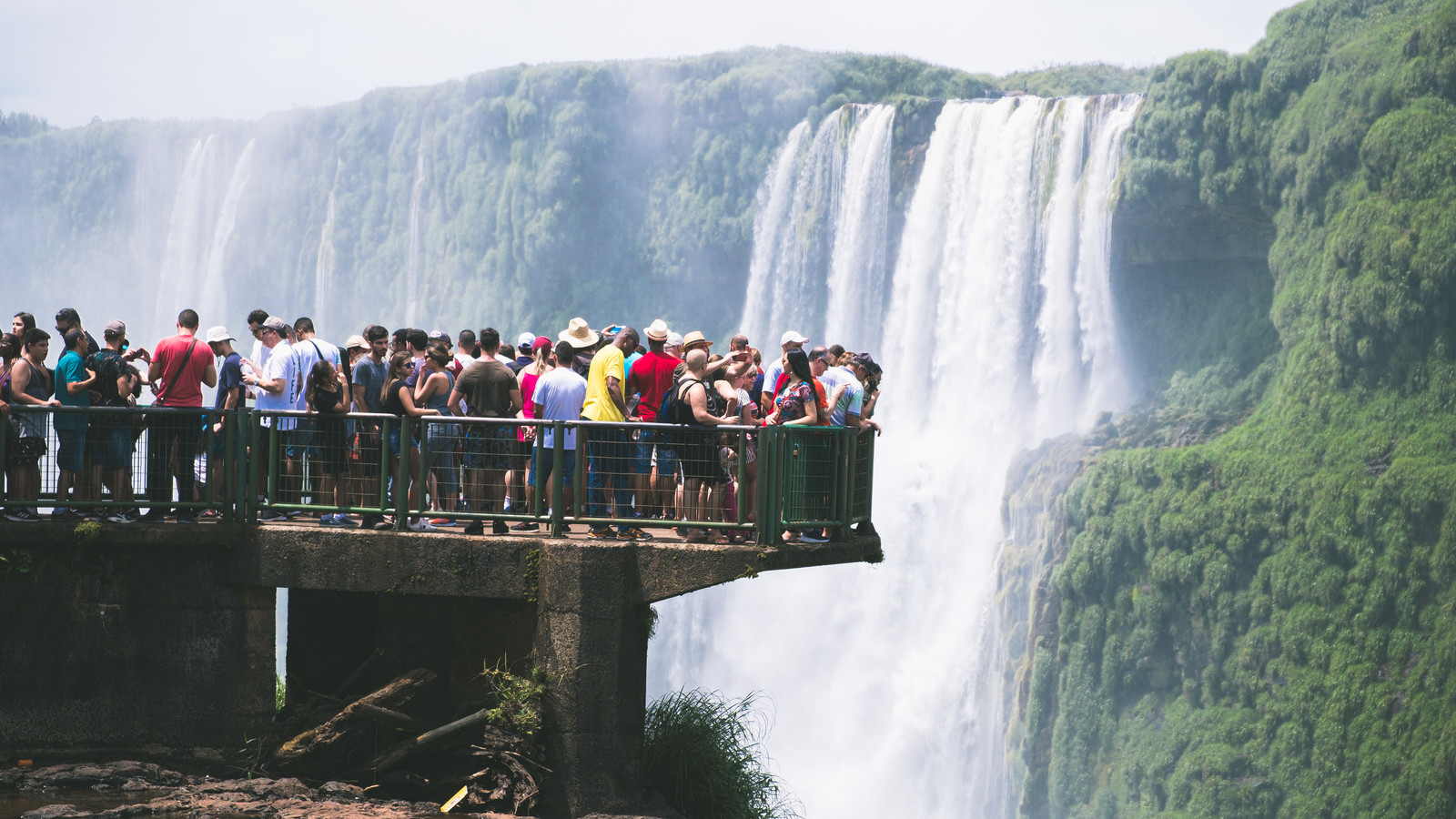 絶景の滝の上に設置された遊歩道と下を覗き見る観光客(イグアスの滝)のフリー素材
