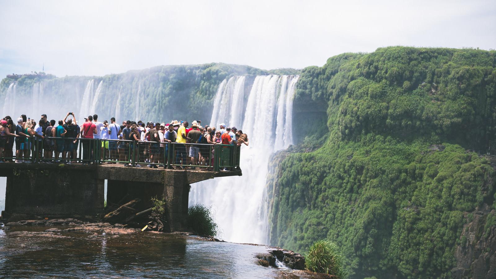 「滝を覗き込むツアー客の集団(イグアスの滝)」の写真